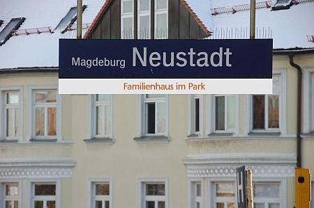 """Bildlegende: Schild """"Bahnhof Neustadt mit Zusatz Familienhaus im Park"""""""